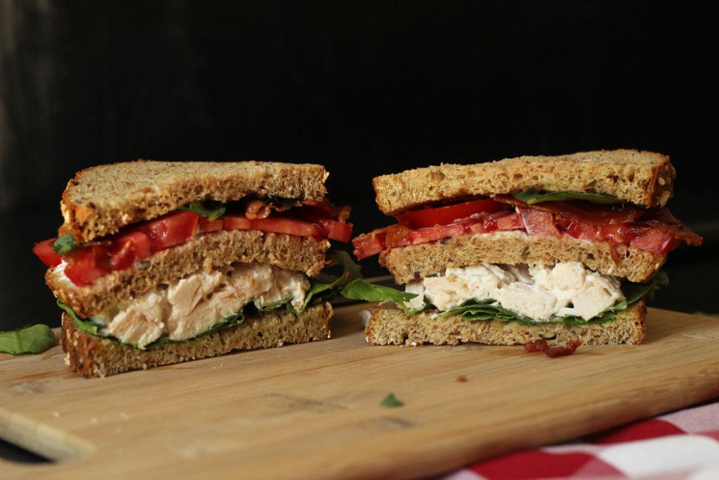sandwich cut in half on cutting board.